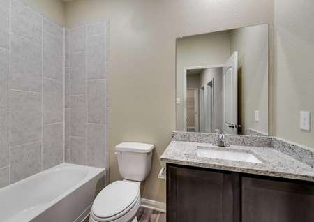 Maple bathroom with white fixtures, granite countertop, and dark wood cabinetry