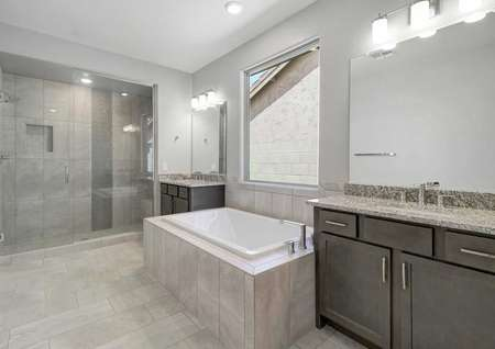 Bartlett master bath with large window above custom bath, two vanities with sinks, and brown cabinet fixtures