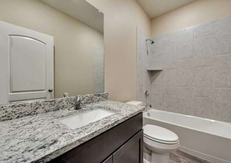 St. Clair guest bathroom with custom tile work, thick granite vanity, and brown cabinet