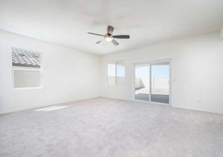 The living room in the Del Mar floor plan with a ceiling fan that has a light, carpet flooring and multiple windows.