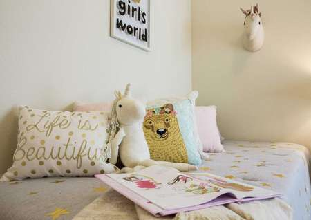 Staged children's room with open book, stuffed animals and throw pillows on the bed.