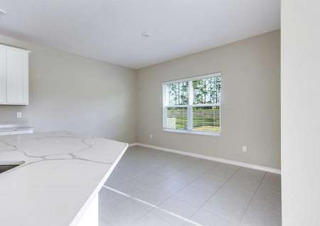 The dining room area that has tile flooring, recessed lighting and a large window in the Mykka floor plan.
