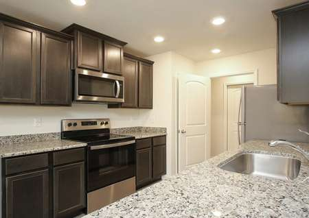 Closeup photo of kitchen with gray speckled granite, single basin stainless sink, dark brown cabinets and stainless appliances.