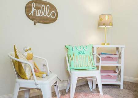 Kid's playroom with wooden sign on the wall, two kid's chairs with pillows and a shelf with lit lamp in the corner.