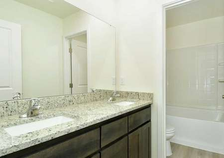 The Northwest Oak second bath room with a dual granite sink and doorway showing the bathtub.
