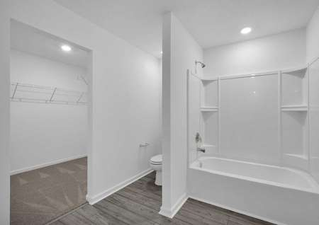 The home's master retreat includes a full bathroom with a large walk-in closet, a toilet and a bathtub.