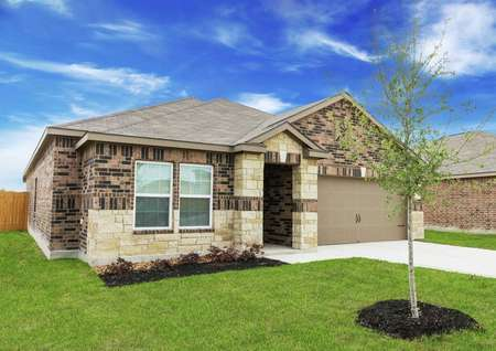 Kendall new home exterior view with landscaped yard, shade tree, and custom finished siding with brick and stone