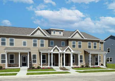 Angled view of the front elevation of a 4-unit townhome building at Huntington Pointe featuring from left to right the Hampton, Carol, William and York floor plans.