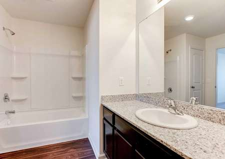 Nicollet bathroom with granite countertops, white sink, and brown cabinet