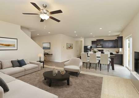 Staged spacious living room with carpet, plank flooring, ceiling fan and adjacent dining room and kitchen and door to backyard, staircase visible.