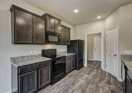 Cypress kitchen with brown cabinets, black appliances, and wood-like flooring