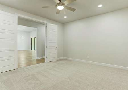 The Mantle features an incredible flex room with brown carpet, a ceiling fan and white walls.