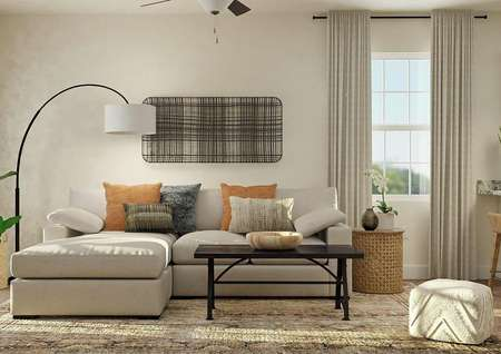 Rendering of the spacious living room in the Maple with tan walls, carpeted flooring and windows. The space is decorated with a spacious couch, standing lamp, coffee table and large rug.