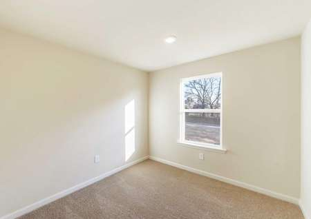 Guest bedroom with recessed lighting and a large window.