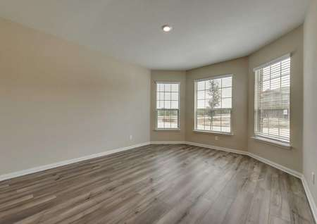 The Texoma floor plandining area with three large windows, tan walls, white baseboards and vinyl wood flooring.