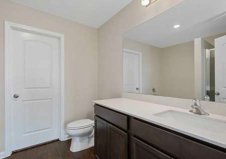 The Clairborne model master bathroom with vinyl wood like flooring with dark brown cabinets with white quartz countertops, a full mirror and toilet in the corner next to a white door