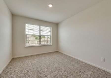 The secondary bedroom has white walls and brown carpet.