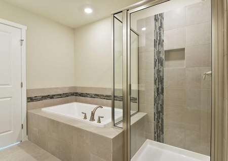 Larch master bathroom with walk-in shower stall, white bathtub, and custom tile work