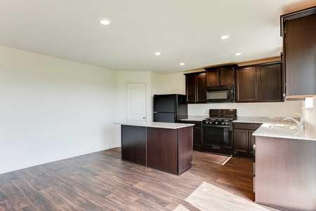 Nicollet kitchen with recessed lights, brown cabinetry, and granite countertops