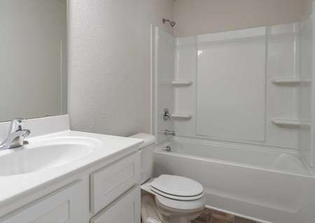 Alamance bathroom with white toilet, bath/shower, and sink fixtures