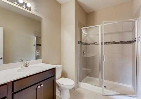 The Mateo model home's master bathroom with dark brown cabinets, tile flooring, a walk-in shower and cultured marble countertops