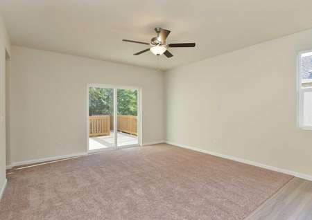 Columbia great room with ceiling fan, white sliding patio doors, and soft carpeted floors