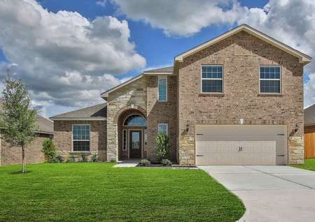 Exterior single-family, two-story brick Marquette model with a two-car garage, stone, front porch, and front yard landscaping
