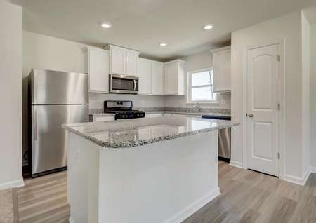 Modern kitchen with white cabinets, polished gray granite, stainless appliances, recessed lighting, window.
