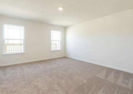 Spacious owner bedroom with carpet, two windows, recessed lighting.