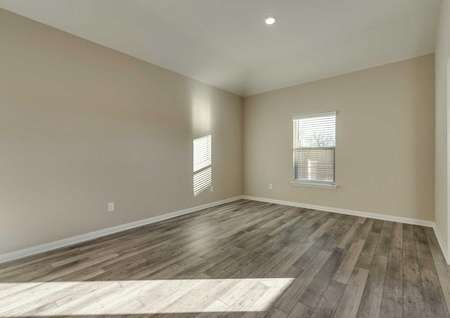 Dining room with brown vinyl floors, tan walls, white trim and a window.