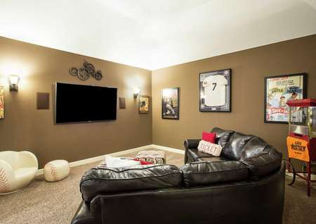 Mantle living room with brown leather couch, dark brown painted walls, and wall art