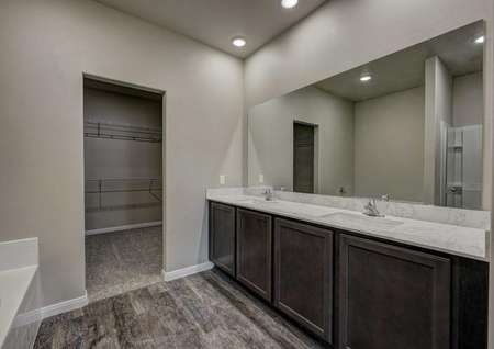 Cypress bathroom with extended vanity, multiple sinks, and brown cabinet