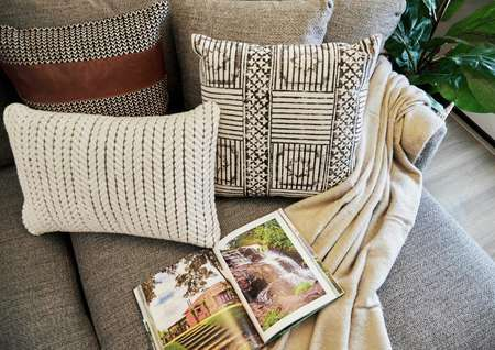 Staged couch with open book, pillows and blanket.