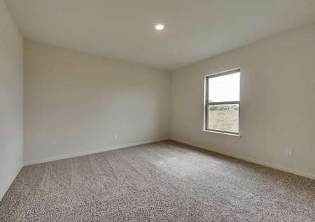 Bedroom in the Topeka floor plan. Carpeted flooring, a window and light fixture in the ceiling.