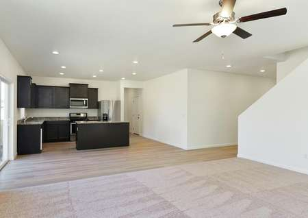 View from open living room with carpet and ceiling fan into dining and kitchen.