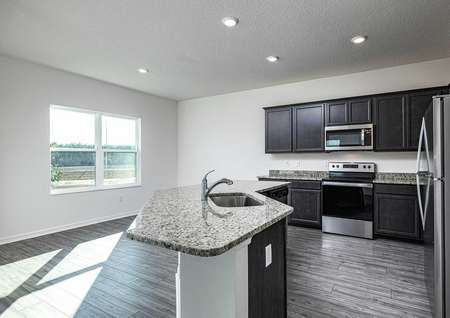 Open-concept kitchen with installed stainless steel appliances and granite countertops.