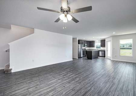 Open-concept entertainment space overlooking the stairs, family room, covered back patio and spacious kitchen area.