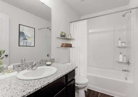 Staged bathroom with single sink vanity, toilet and tub-shower combo with white shower curtain, dark flooring and frameless mirror.