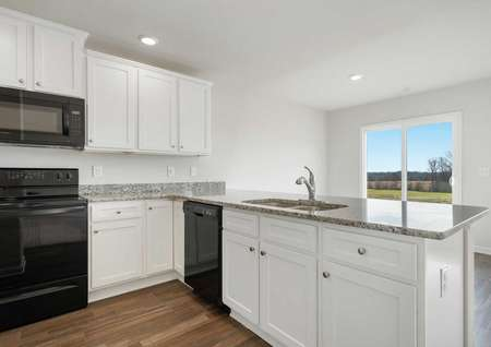 Ashley kitchen and dining area with granite counters, black appliances, and wood floors