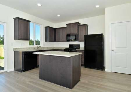 Cypress kitchen with granite counters, wood cabinets, and recessed lights