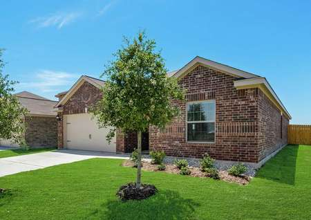 Whichita completed house with grass and trees in front yard, custom brick finish, and wood fence
