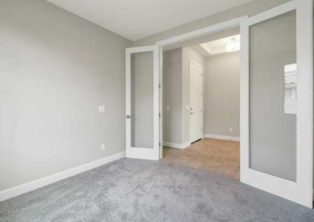 Hawley finished floor plan with carpeted floor, French style glass doors with wood frame, and grey walls