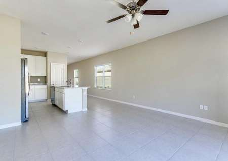 The open living room with tile flooring, a ceiling fan in the Alafia floor plan.