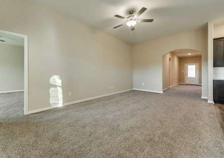 Family room with tan walls, white trim and brown carpet.