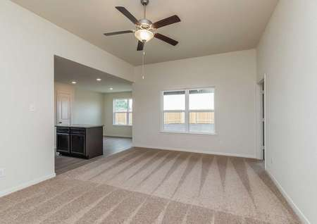 Blanco great room with brown carpets, access to the kitchen and dining area, and overhead ceiling fan with light