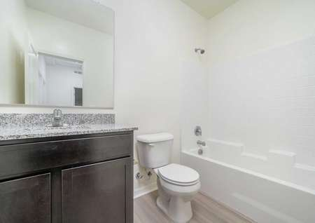 A secondary bathroom in the Del Mar floor plan with brown cabinet hardware, granite countertops and a tub/shower.