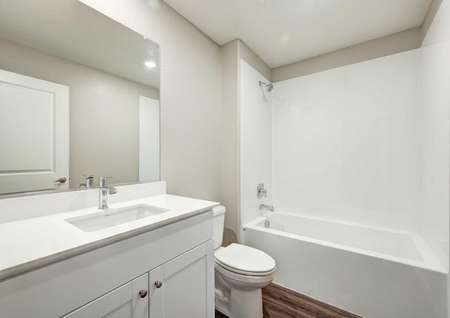 A bathroom with a bathtub/shower combo, white cabinets and cultured marble countertops.