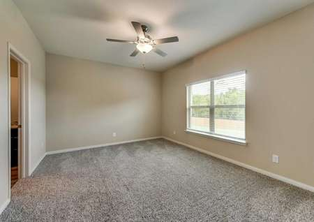 Master bedroom with tan walls, brown carpet, white trim and a ceiling fan.
