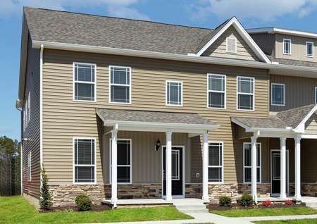 Straight-on view of the front elevation of the Hampton townhome at Huntington Pointe, featuring tan paint with white trim and water table height ledgestone along front exterior.