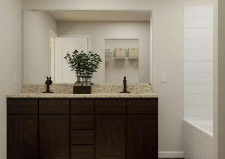Rendering of the master bath focused on a   double-sink vanity with brown cabinets and a mirror. The shower is visible on   the right.